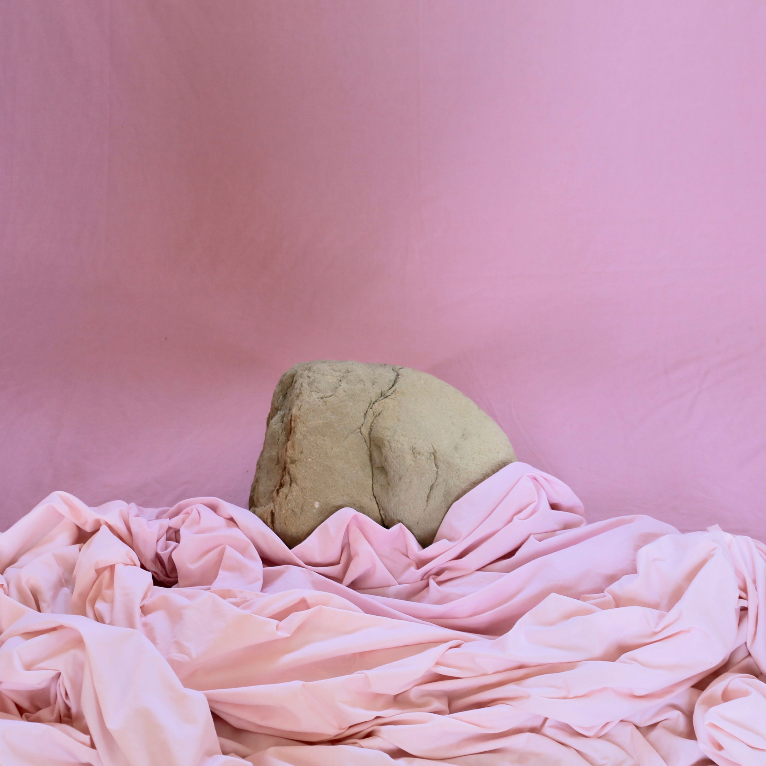 A grey rock in the shape of an arse propped up theatrically against a dusty pink wall and draped in pink sheets.