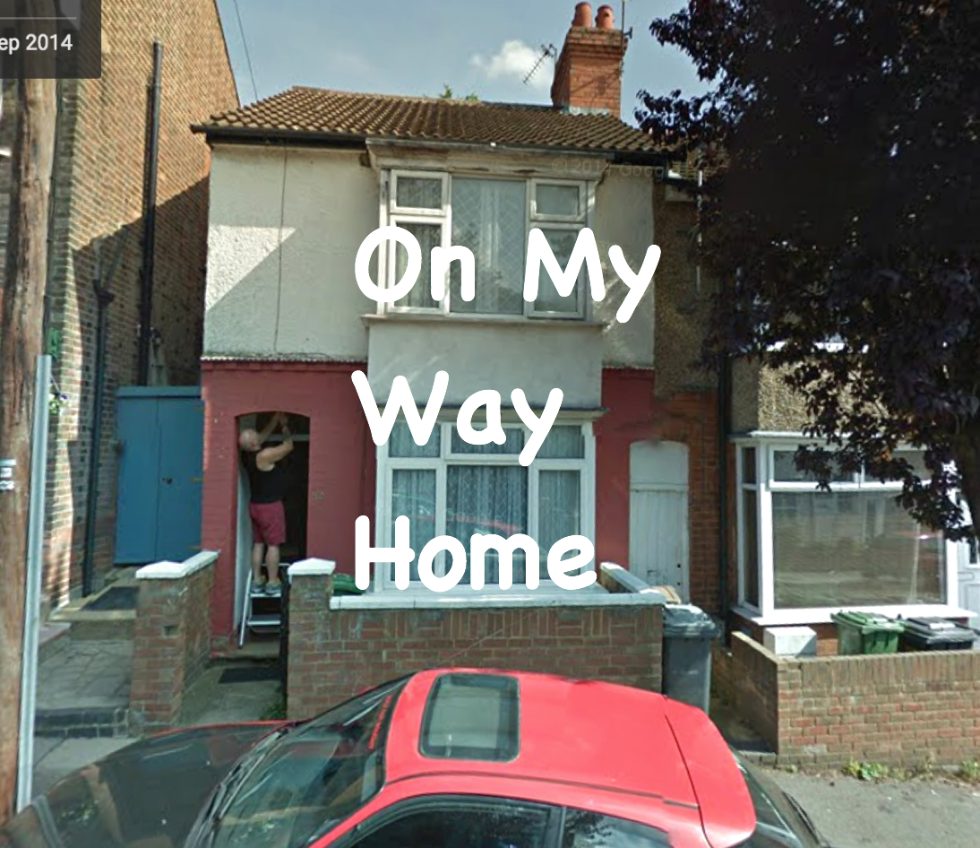 Photograph of a person fixing up a doorway of a semi-detached house formed of multiple cream- and salmon- coloured panels. A red car with a skylight parked outside. Caption in Comic Sans going across the centre of the image reads On My Way Home