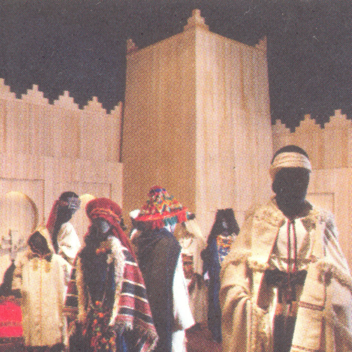 Scan of an image of a group of figures in traditional Berber dress, beige and gold fabric with colourful patterns sat against a wooden architectural structure of Berber provenance.