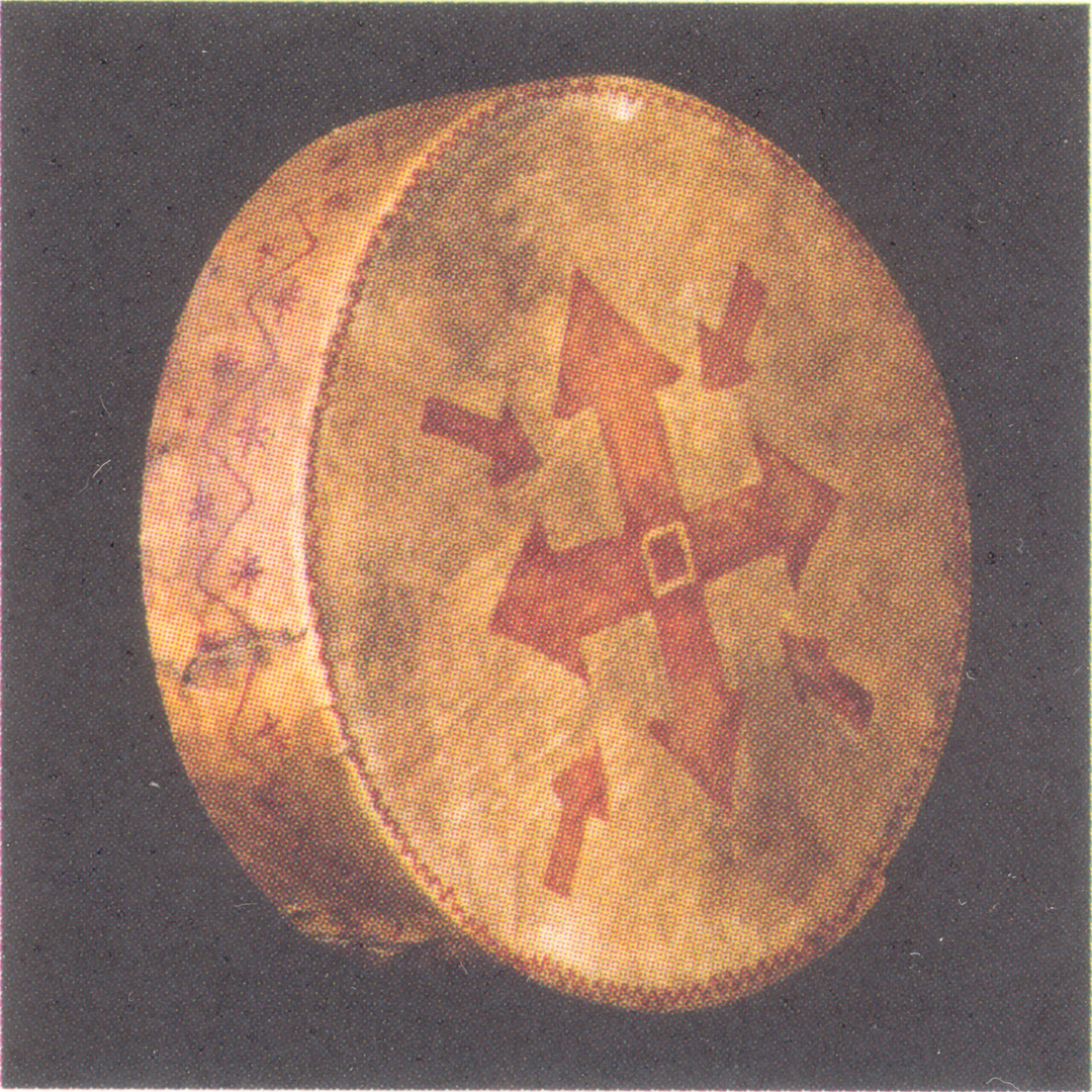 Image of a small and relatively flatcylindrical drum / sacred cultural object with an inscription of an arrowed cross on it in red. Scanned in from the Berber museum catalogue.